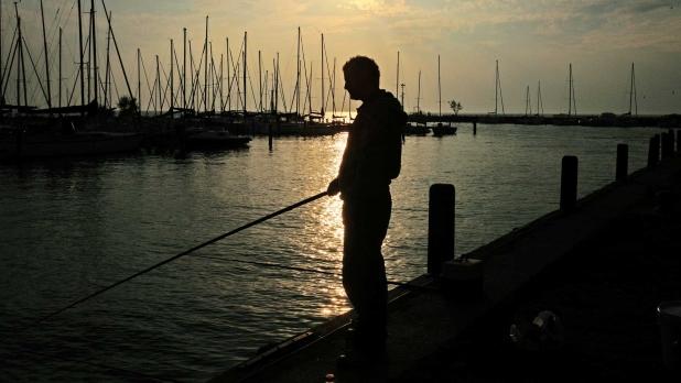 Telihold okozta ezüsthíd a Balatonnál, horgász sziluettjével.